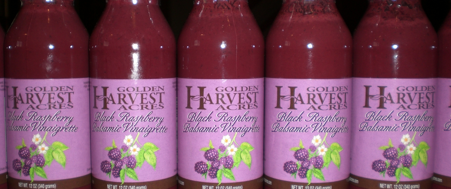 "A close up of a line of glass bottles on a red countertop. The bottles have gold colored metal lids, and are filled with a purple, red substance. The bottles have light purple labels that show black raspberries, leaves and flowers and reads ""Golden Harvest Acres Black Raspberry Balsamic Vinaigrette"""