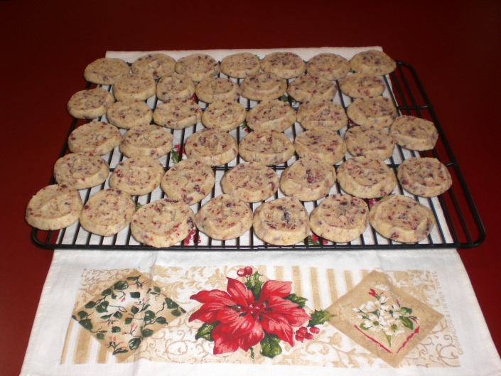 A white tea towel with a poinsettia design sits on a red countertop. A black metal baking rack sits on the towel. The baking rack is full of Cranberry Orange Shortbread Cookies. The cookies are round, tan in color and have red cranberries in them.