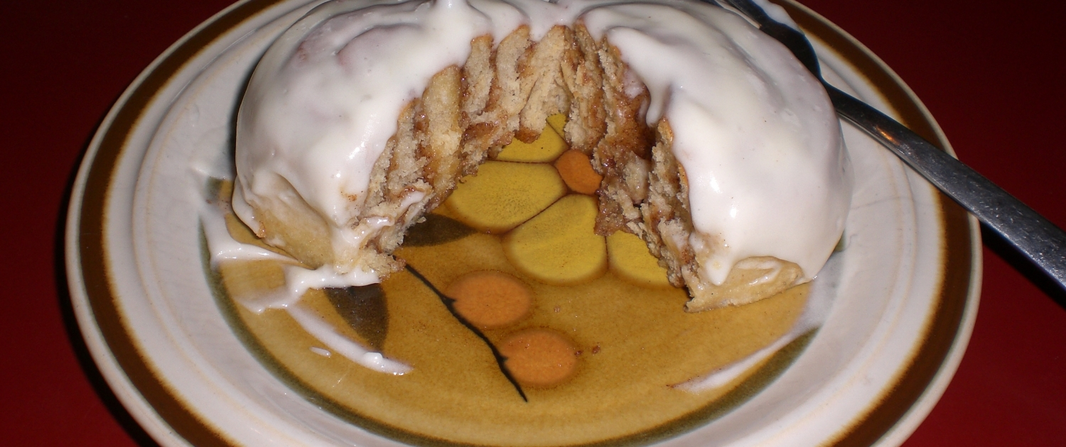 A ceramic plate sits on a red countertop. On the plate is a fork and a cinnamon bun. The bun is cut in half, revealing the cinnamon swirls. The bun is covered in a thick, white icing.