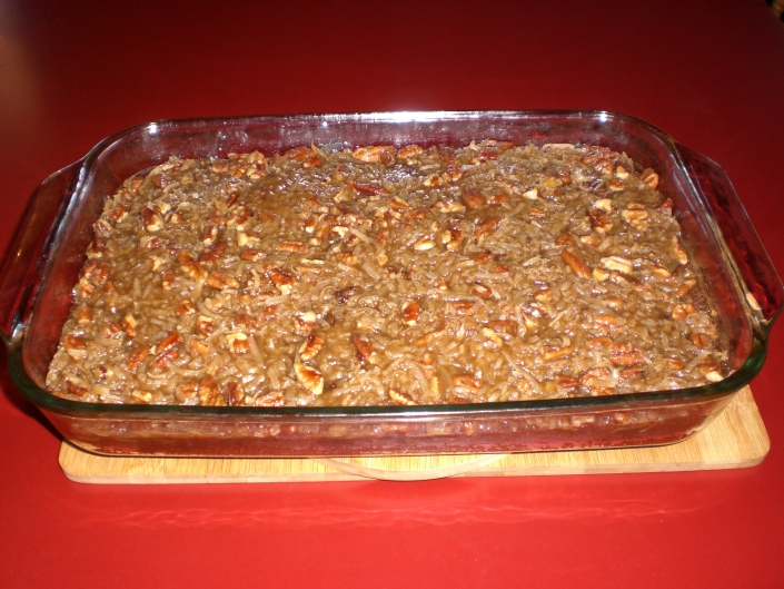 Wood cutting board on a red countertop. The cutting board has a glass baking dish on it. The baking dish is full of Oatmeal Streusel Cake. The cake is brown and has a golden brown topping with visible pieces of walnut.