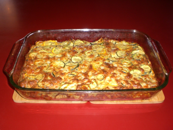 A Zucchini Bake in a glass dish. The dish sits on two wooden cutting boards on a red countertop. The zucchini bake has a golden brown crust and pieces of green and yellow squash are visible.