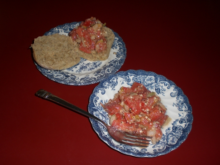 Two porcelain dishes with blue and white flourishing. One plate has a fork and bruschetta (a mixture of tomatoes, garlic etc.) The other plate shows toast topped with the bruschetta.