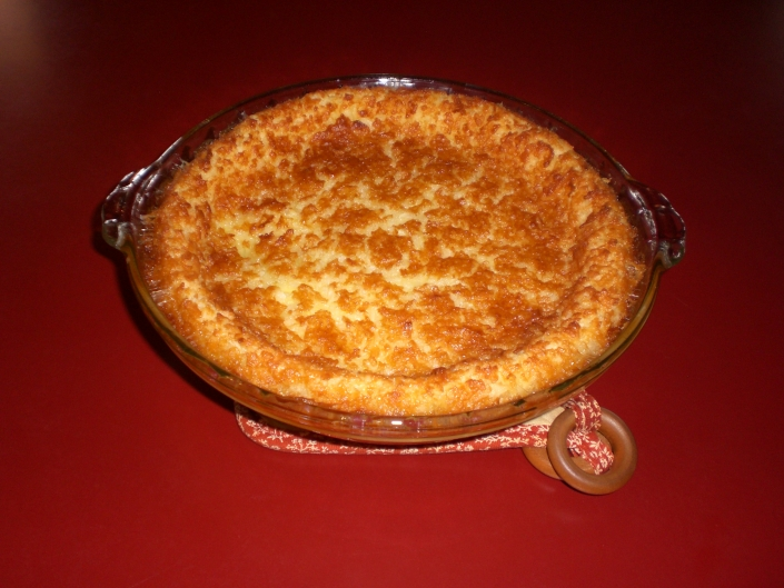 A Coconut Miracle Pie in glass pie dish. The dish sits on a patterned fabric trivet. The trivet and dish sit on a red counter. The pie is tan with a crackled, golden crust.