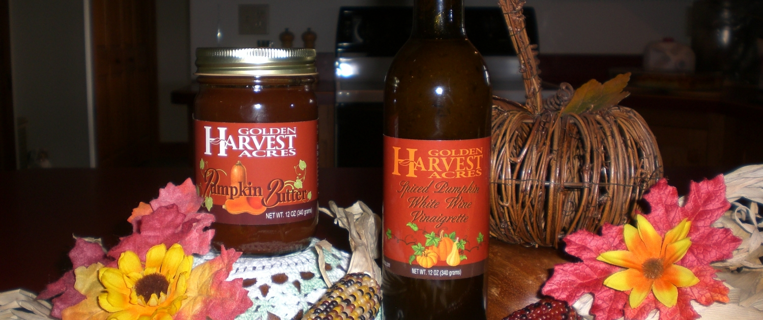 """A scene on a kitchen counter shows a glass jar and a glass bottle. The glass jar has a gold lid and is filled with a brown spread. The glass jar has an orange label, showing a halved butternut squash and vines. The label reads """"Golden Harvest Acres Pumpkin Butter."""" The glass bottle is tall and tinted, with a purple foil wrap on the cork. The bottle is filled with a dark liquid. The bottle has an orange label, showing three different pumpkins and vines. The label reads """"Golden Harvest Acres Spiced Pumpkin White Wine Vinaigrette."""" The bottle and jar are surrounded by fall decorations, like a wicker pumpkin, red and orange leaves, fall flowers, and dried decorative corn."""