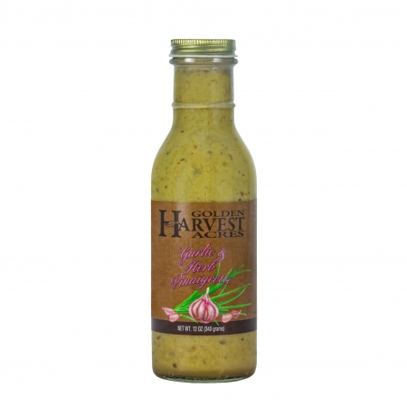 """A glass jar with a gold lid. The jar is filled with a tan liquid with multicolored speckles. A brown label shows garlic and fresh herbs. The label reads """"Golden Harvest Acres Garlic & Herb Vinaigrette Net Wt. 12 oz (340 grams)"""""""