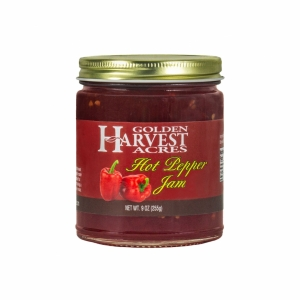 """Glass jar with gold lid. Jar is full of red jam with a few white speckles. A red label shows bright red peppers. The label reads """"Golden Harvest Acres Hot Pepper Jam Net Wt. 9 oz (255g)"""